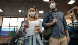 Coronavirus outbreak. Traveling couple go down escalators wearin